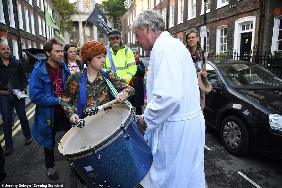 The Conservative Lord is pictured confronting a young activist banging a drum outside his home