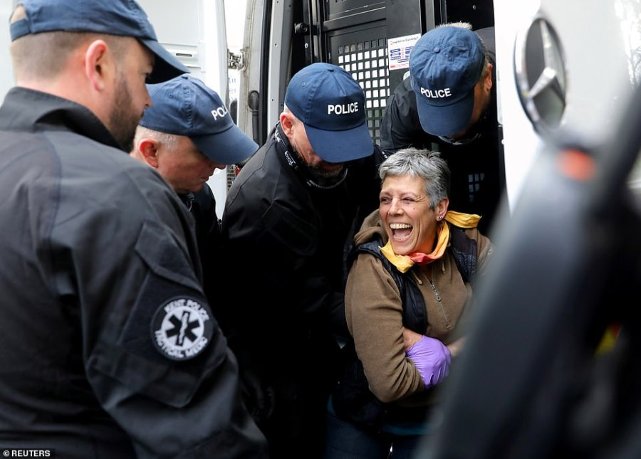 A woman laughs with supporters as four police officer drag her to the van after she refused to leave the area outside th Home Office