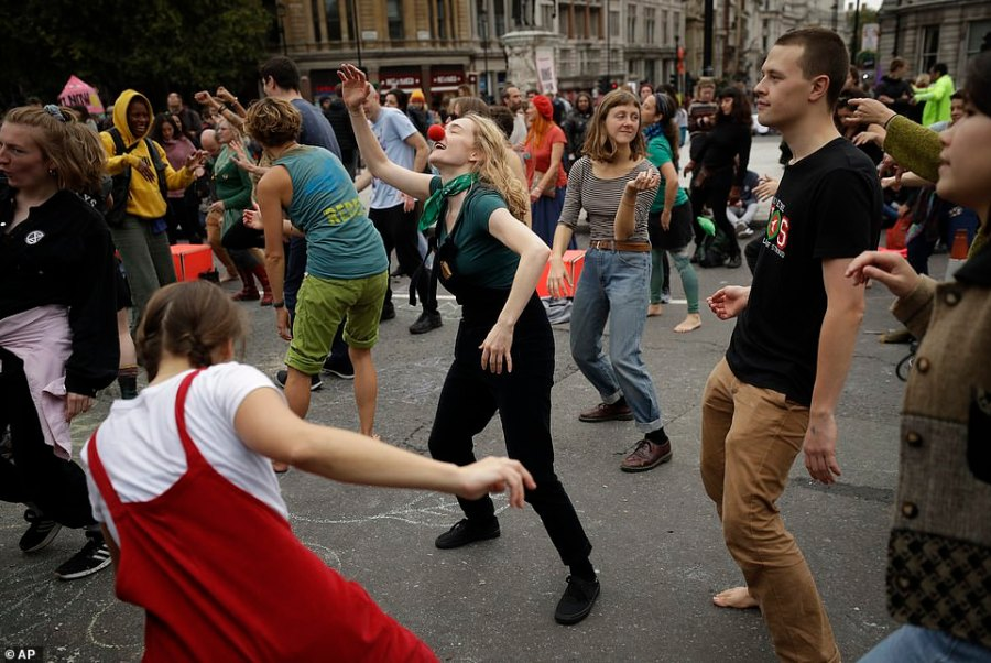 Extinction Rebellion climate change protesters dance to music as they block a street at the bottom of Trafalgar Square without arrest
