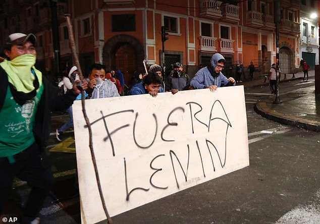 Protesters in Quito on Monday protect themselves from tear gas and hold up a banner which translated to English says 'Out Lenin'