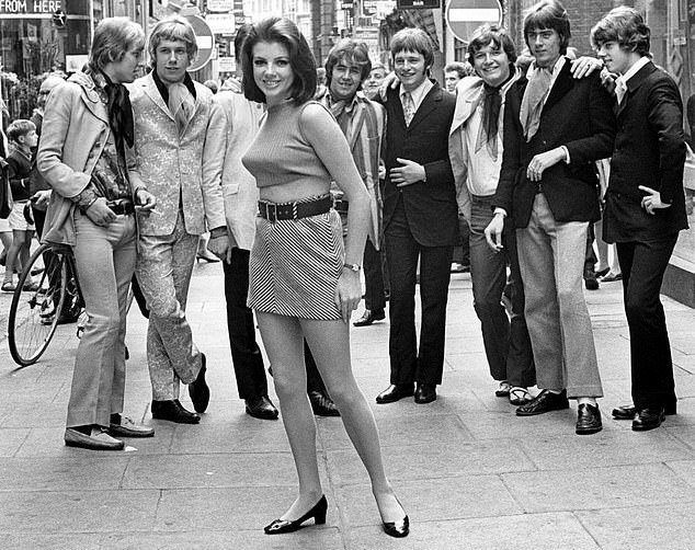 Virginia Nicholson said women in the 1960s still believed sex was intertwined with love and would be 'shocked' at today's casual 'hook-up' culture using apps such as Tinder. Pictured, a group of men looking at a woman wearing a miniskirt on Carnaby Street, London in the 1960s