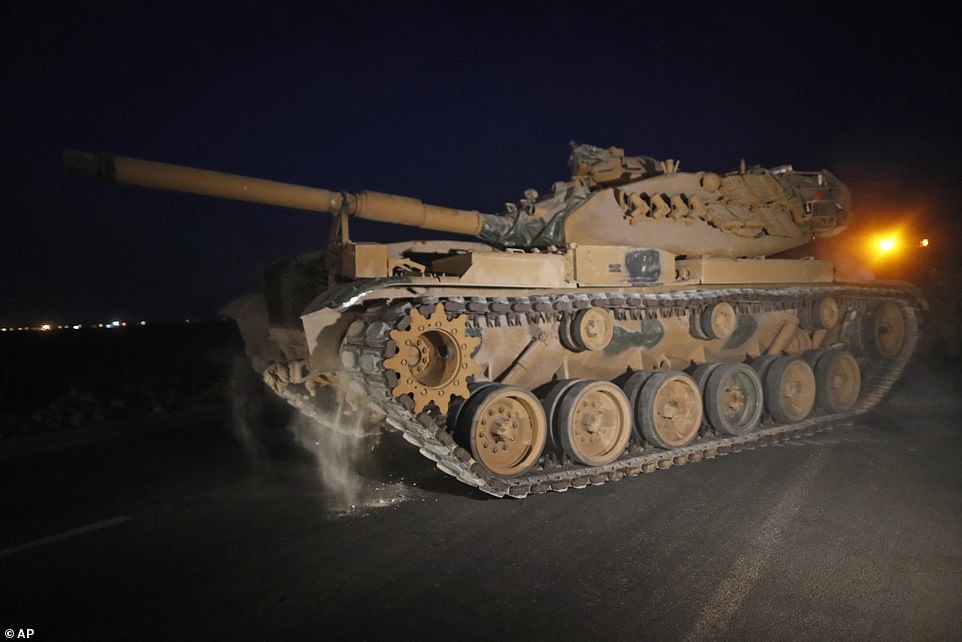 Two small expeditionary forces of Turkish troops moved into northern Syria on Wednesday morning, an official claimed, ahead of a much larger invasion (pictured, a tank near the border overnight)