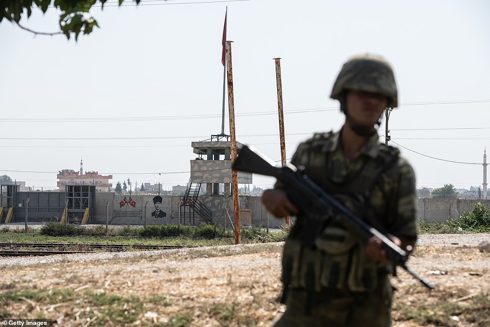 A wall separating Turkey from Syria is seen behind a Turkish soldier who stands guard inAkcakale, close to where an expeditionary force is said to have crossed into Syria early on Wednesday