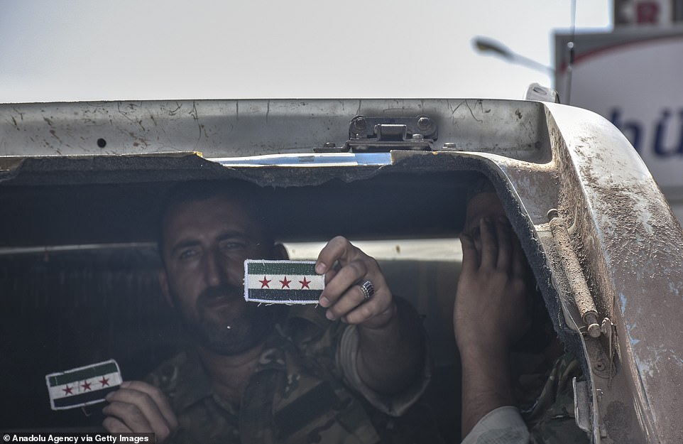 Members of Syrian National Army (SNA) hold up patches as they make observations with Turkish Armed Forces at the Syrian border in Akcakale district of Turkey's Sanliurfa today