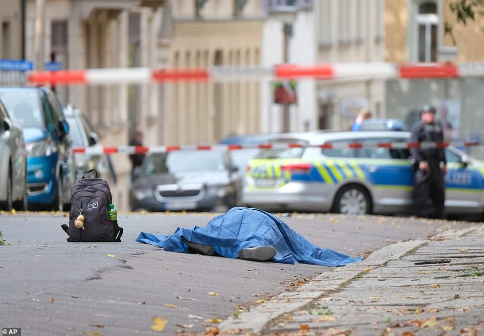A body lies in the street outside the synagogue, believed to be that of a female passerby who was gunned down when an attacker failed to get into the synagogue