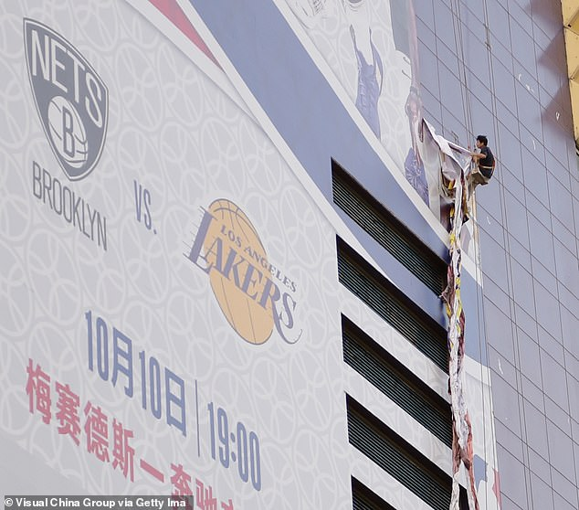 A worker removes a large poster from a building ahead of NBA Shanghai Game 2019 between Brooklyn Nets and Los Angeles Lakers at the Lujiazui Zhengda Plaza