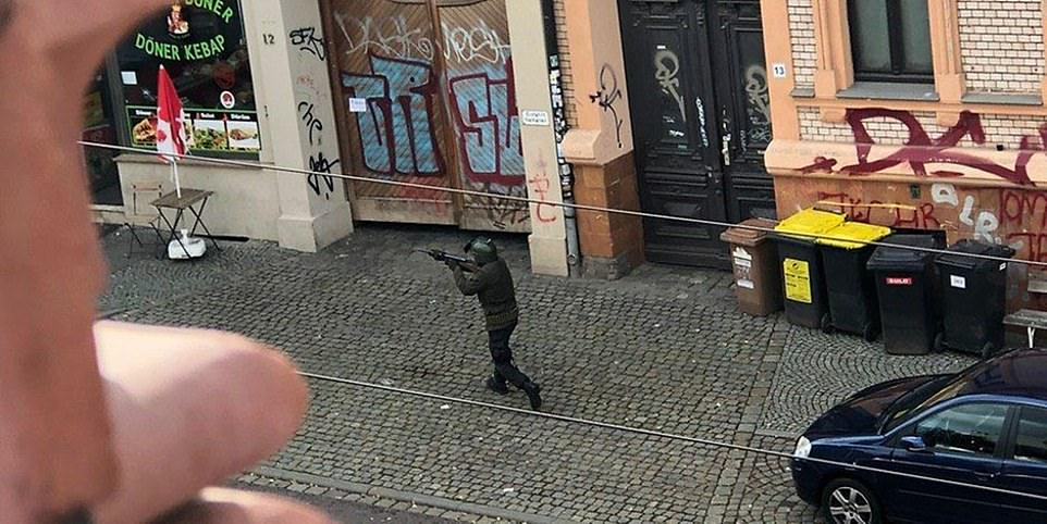 A man and a woman were shot dead in an attack on a synagogue in Halle, central Germany, on Wednesday, while several others were injured. A gunman is pictured outside a kebab shop close to the synagogue