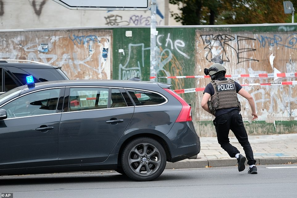 An armed officer runs to his vehicle in Halle. Police say they have arrested one suspect and are looking for others