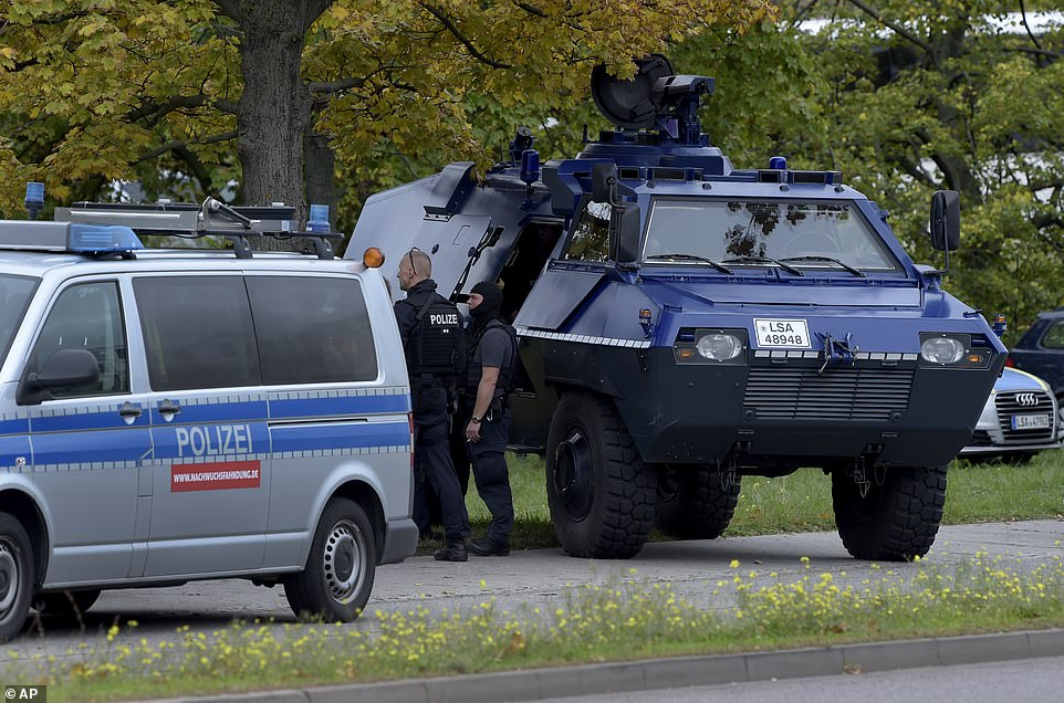 Police officers with an armoured vehicle block a road in Halle, Germany