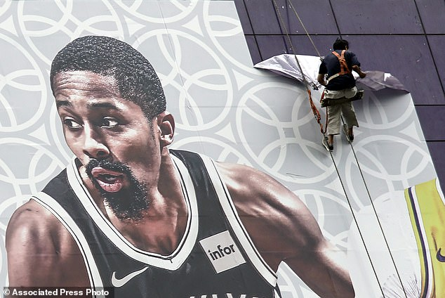 Chinese workers are seen ripping down an NBA billboard advertisement on Wednesday after the nation's state broadcasters vowed not to air this week's preseason games in China