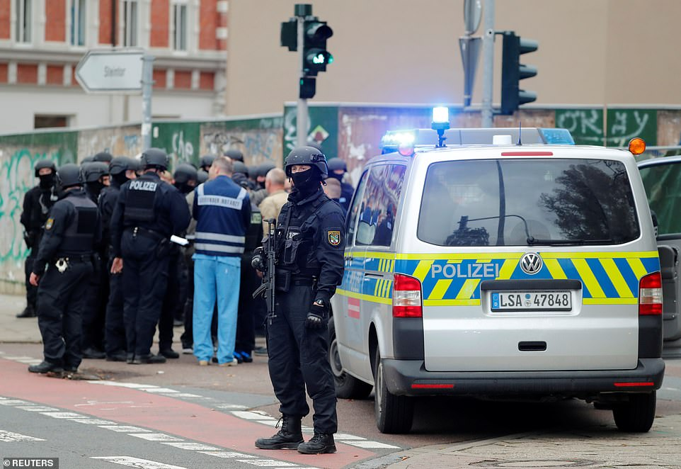 A police officer stands guard next to a van close to which his colleagues are gathered near the site of the shooting in Halle
