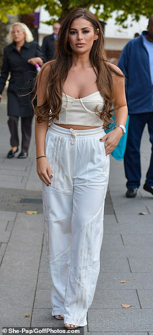 Sports luxe: Courtney, 24, showed off her sartorial flair in a bandeau cream crop top and shiny white joggers