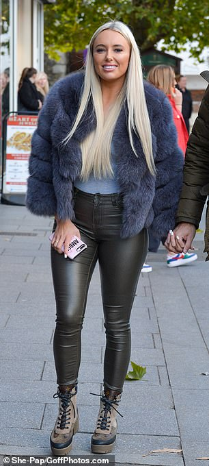 Outfit change: The reality star, 26, arrived at Bloc 40 nightclub hand-in-hand with Dan in leather leggings and a plush blue coat