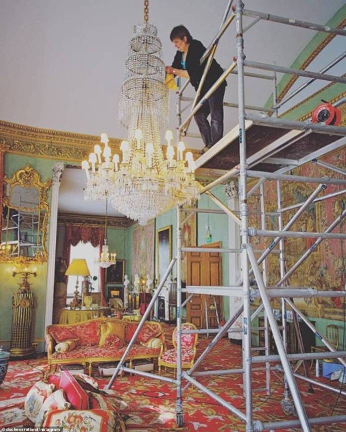 A housekeeper cleans the large living room in the spring - and needs a scaffolding to reach the chandelier in the room with the high ceiling