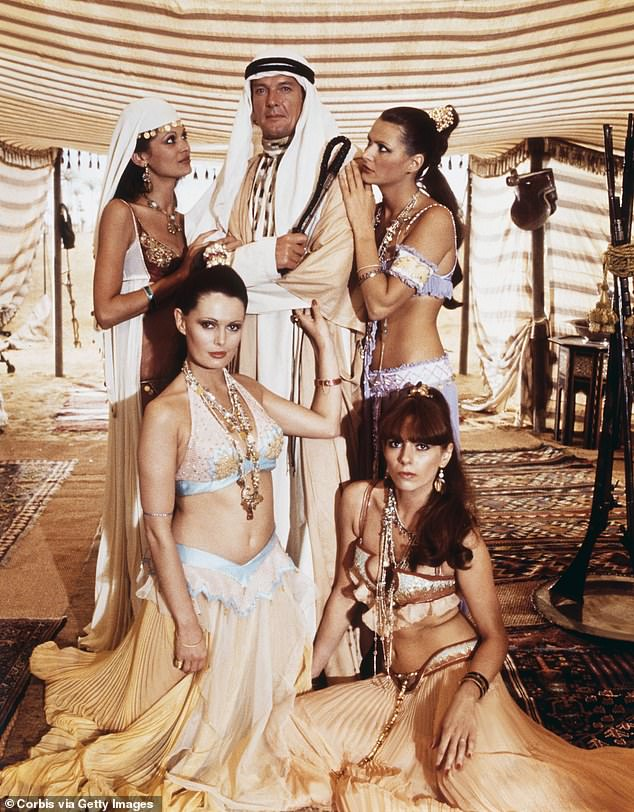 James Bond actor Roger Moore with four women on the set of 10th film The Spy Who Loved Me in 1977