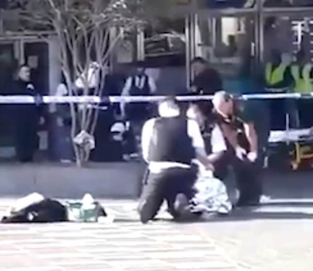 Police and paramedics found Baptista with 'critical injuries' and despite battling to save his life he was pronounced dead at the scene near the shopping centre at 3.49pm. Pictured: Police treat the surviving teenager in Stratford