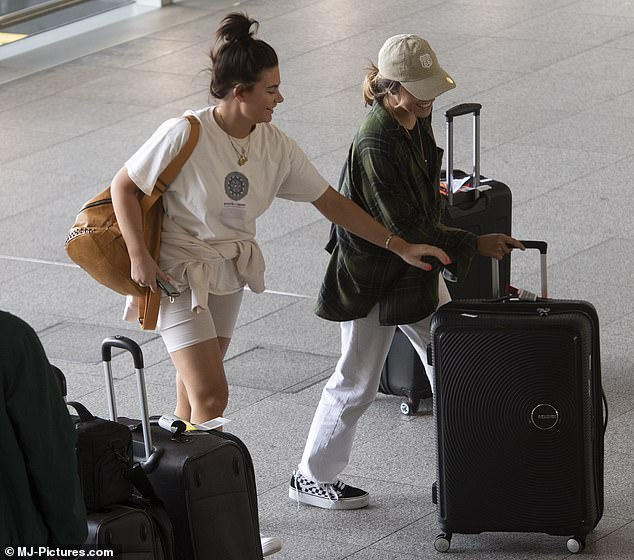 Travel buddies: Megan laughed as she tried to take one of the black suitcases from Chelcee