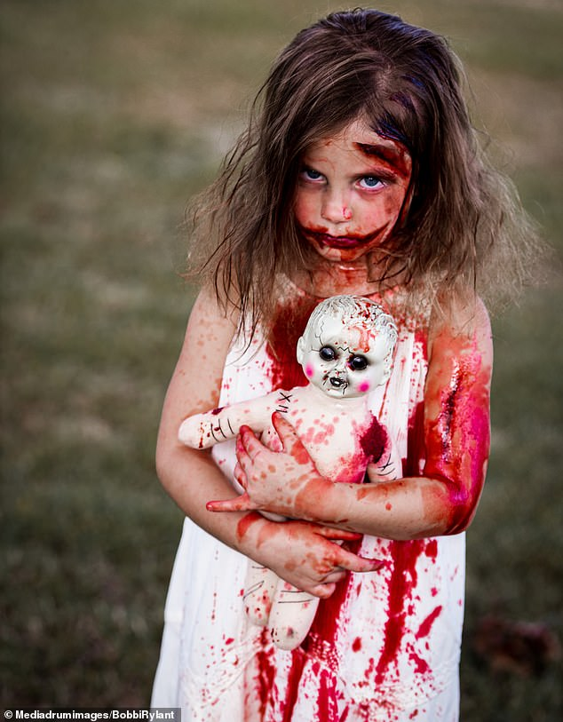 Striking shots show five-year-old Kynadee in full zombie Halloween make up snarling at the camera