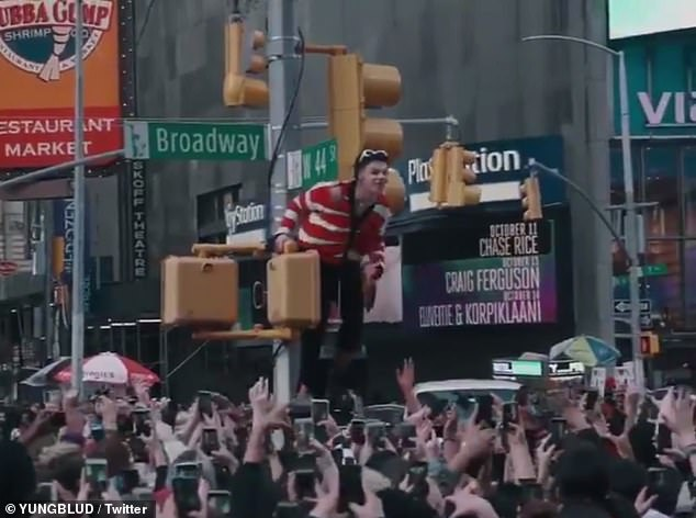 Dominic Harrison, known as Yungblud, climbed a traffic light pole before jumping into the crowd in central New York yesterday