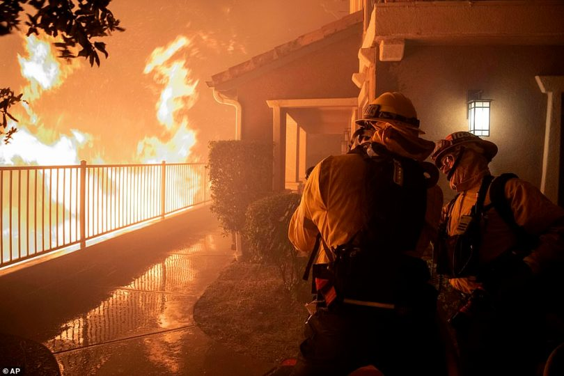 Firefighters work on a hose nozzle as the Saddleridge fire burns nears homes in Sylmar on Thursday