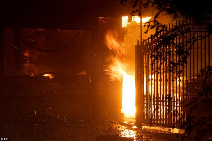 Flames shoot out from the front of a house on Jolette Way in Granada Hills North early Friday morning