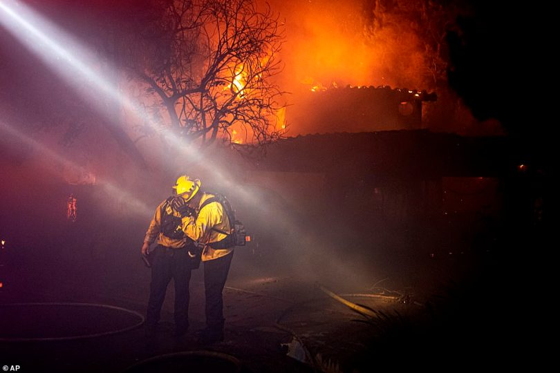 Firefighters recoil from smoke and heat from a fully engulfed house on Jolette Way in Granada Hills North early Friday morning