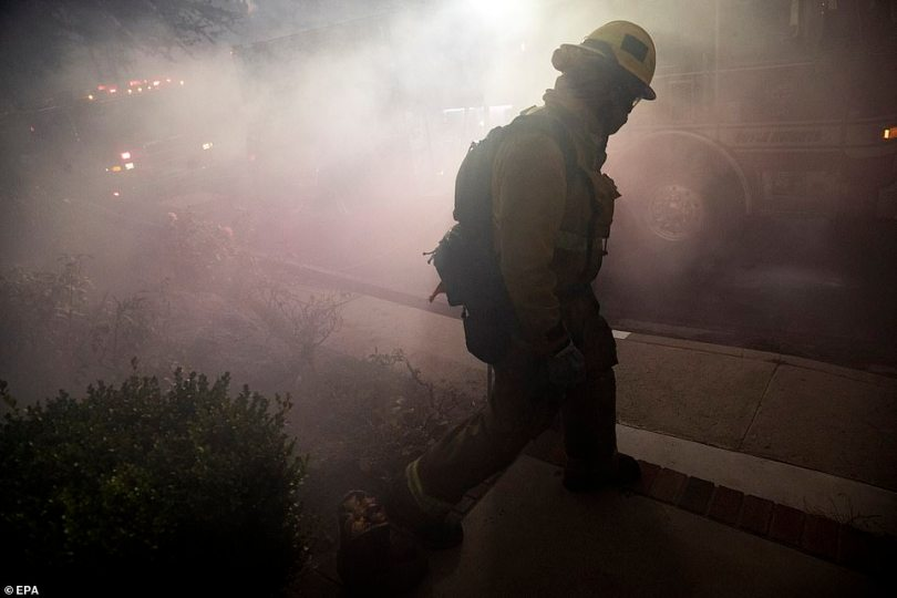 A firefighter walks through the smoke after battling the Saddleridge Fire all night inPorter Ranch on Friday