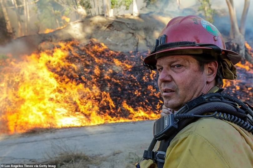 A firefighter keeps an eye on the wildfire burning behind Olive View Medical Center in Sylmar on Friday