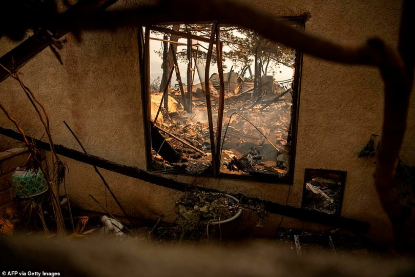 A burned home smolders on Friday after flames from the Saddleridge Fire tore through the region in Granada Hills the previous night