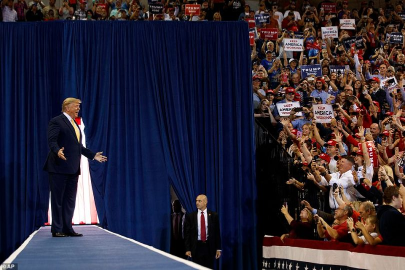 Trump gestures as he arrives to speak at a campaign rally at the Lake Charles Civic Center