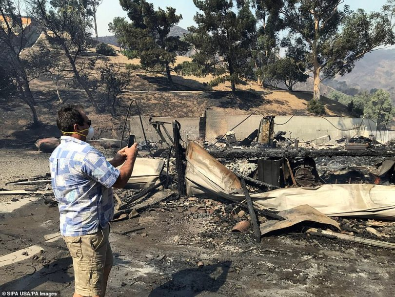 A Porter Ranch man takes a photo of his neighbor's demolished home in the aftermath of the destructive Saddlerdidge Fire that began Friday