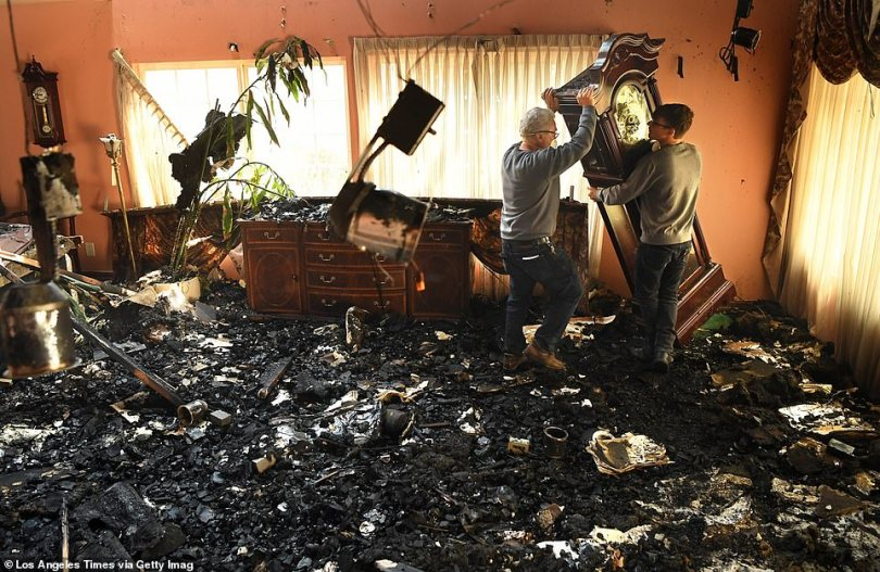 A Porter Ranch man, Jesse Stancaronere (left), enlists the help of his grandson, Jesse Lasher (right), to move a grandfather clock thatmiraculously survived the raging fire that scorched other parts of the home on Friday