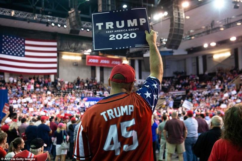 """A supporter holds up a sign as the US president speaks during a """"Keep America Great"""" rally at Sudduth Coliseum"""
