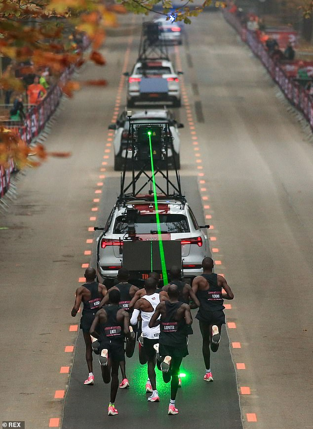 Kipchoge and his pacemaking team follow the timing vehicle as it emits a green laser