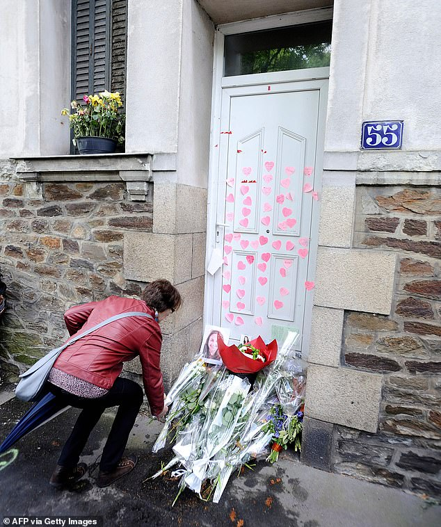 This file, taken on April 14, 2012, shows people laying flowers in front of the Dupont de Ligonnes family home as part of a silent march in the streets of Nantes, western France