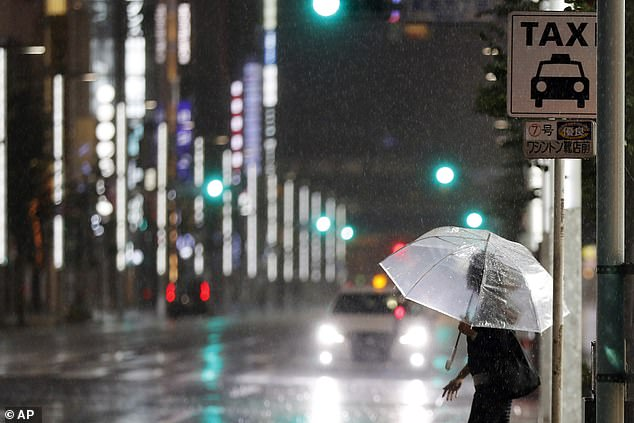 A woman tries to catch a taxi in the pouring rain as Typhoon Hagibis hits Tokyo
