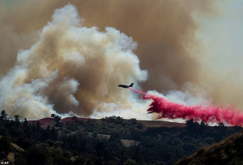 A tanker drops retardant on the Saddleridge Fire burning in Newhall, California, on Friday