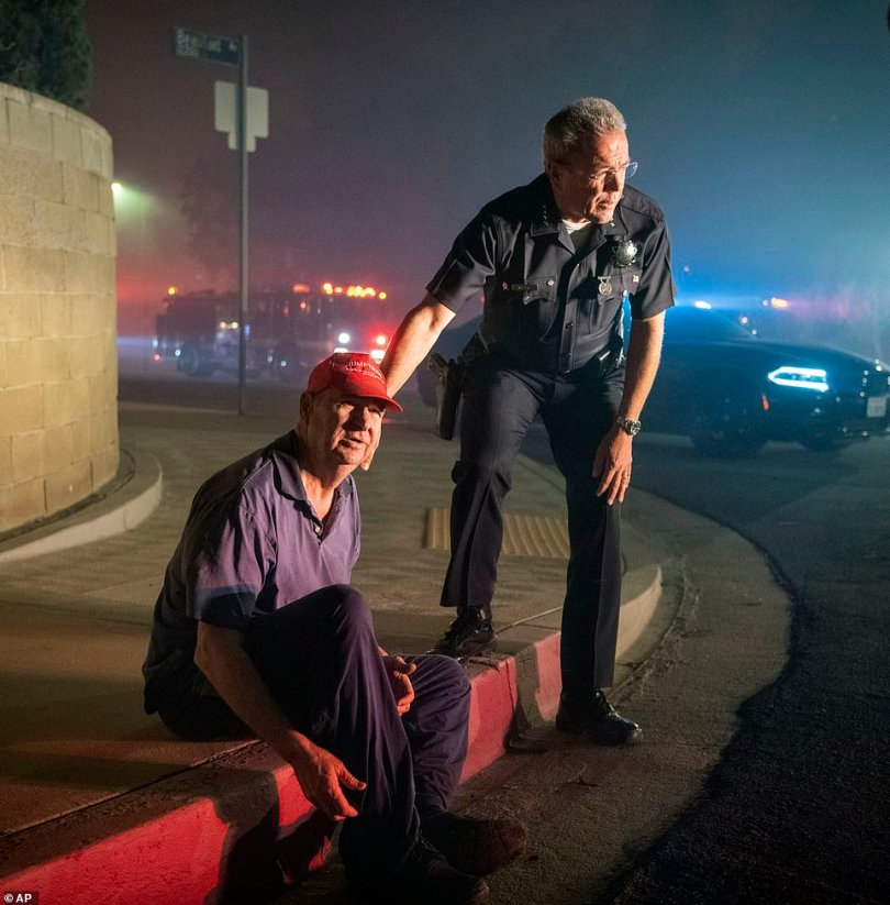 A police chief and Granada Hills resident wait for firefighters to come fight the blaze at the man's home