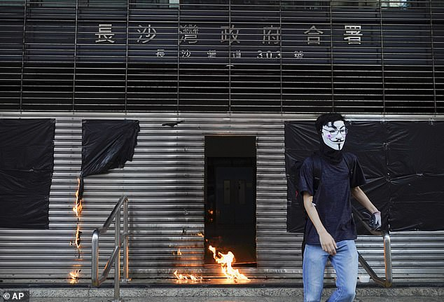 A protester throws a petrol bomb at the entrance of MTR station during a protest in Hong Kong