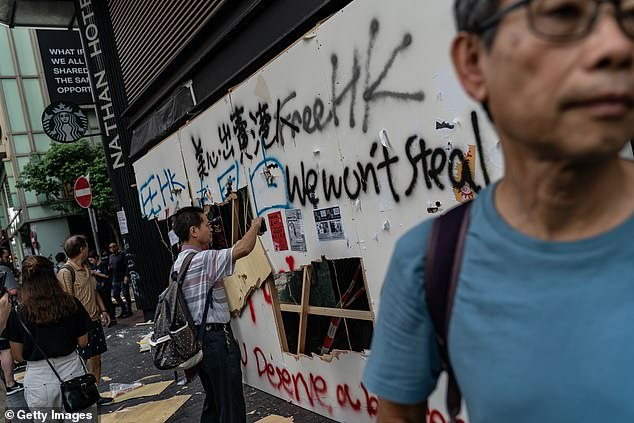 Pedestrians take photographs with their phone of a vandalized Starbucks in Yau Ma Tei