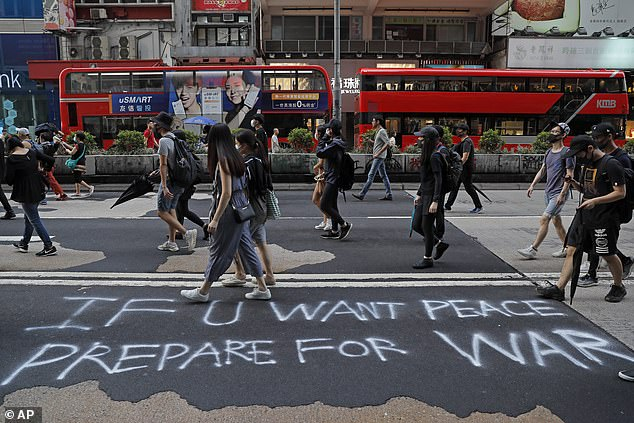 A sign on the ground reads 'if you want peace prepare for war' as demonstrators walk through  Hong Kong