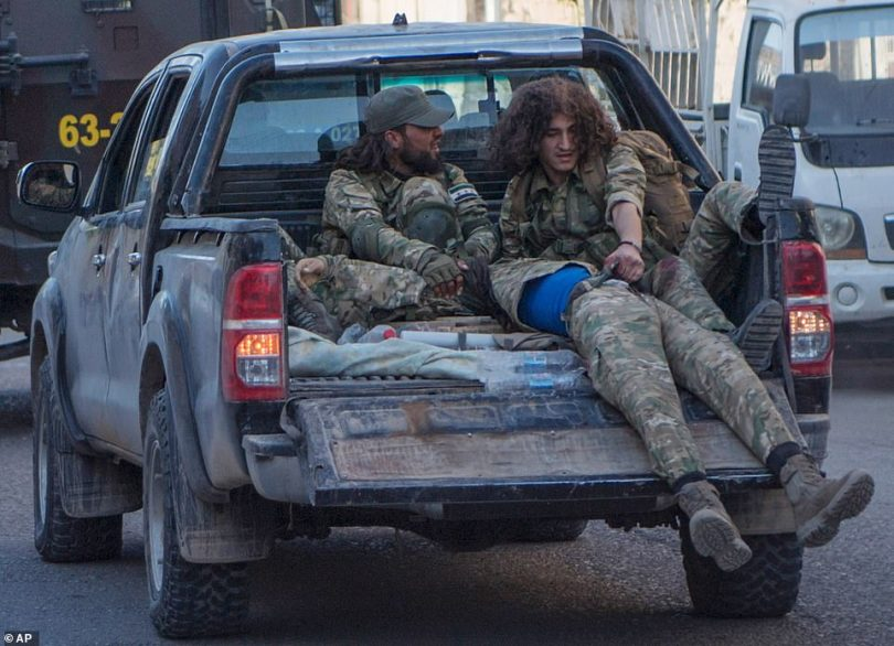 Turkish-backed Syrian opposition fighters evacuate an injured fellow combatant as they return on a pickup truck from Tel Abyad