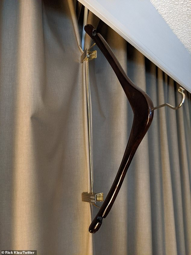 Fasten curtains together using the clips of a coat hanger to stop light streaming into your hotel room