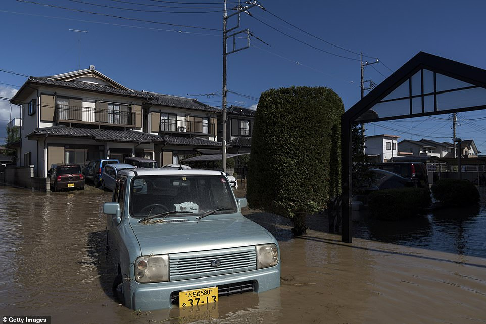 Houses and vehicles sit partially submerged in floodwater following the passage of Typhoon Hagibis on Sunday