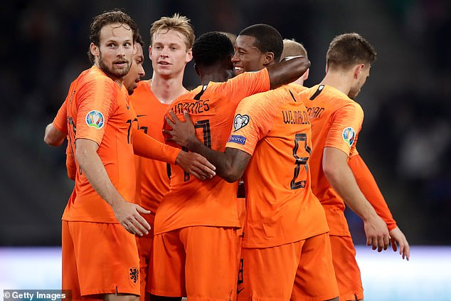 Wijnaldum is congratulated by his Holland team-mates after his second goal of the game