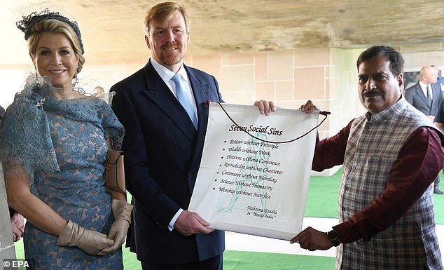 King Willem-Alexander of the Netherlands and Queen Maxima also posed with a scroll listing the several social sins- a list of character traits that are seen to harm society