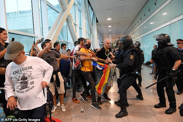 Protesters are pictured clashing with Spanish police inside El Prat airport in Barcelona.Hundreds of students and civil servants also began protesting in different parts of the city