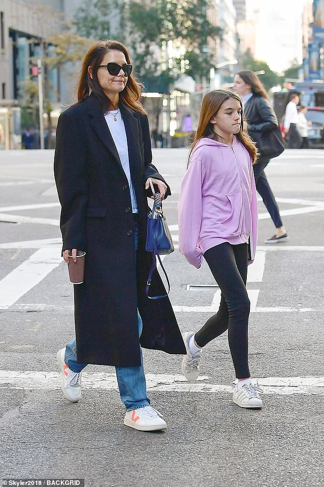 Busy day out:Suri cut a casual figure in leggings with a pink sweater, adding Adidas sneakers; Katie rocked jeans with a white T-shirt, adding a black coat