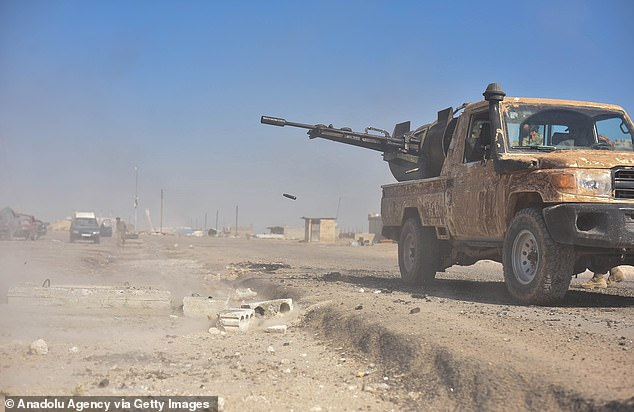 SNA) member fires at targets in Syria's Ras al-Ayn rural after the city center was cleared