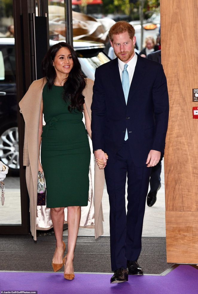 Meghan Markle has re-cycled her wardrobe - dressing in her £462 engagement dress and the coat she wore to Sandringham at Christmas, as she arrived hand-in-hand with Prince Harry for the WellChild Awards tonight